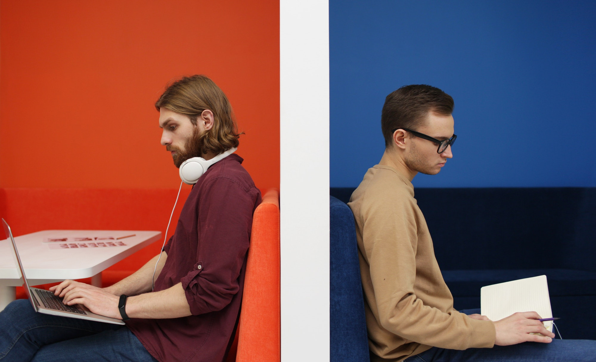 Man with laptop and man with book
